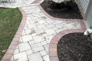 Curved stone pathway transition between patio, side, and front doors